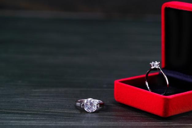 Bouchent la bague en diamant dans une boîte à bijoux rouge