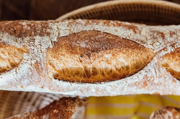 Bouchent la baguette fraîchement cuite dans le panier sur la table en bois. fabriqué par artisan.