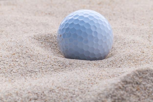 Bouchent la balle de golf dans le bunker de sable à faible profondeur de champ.