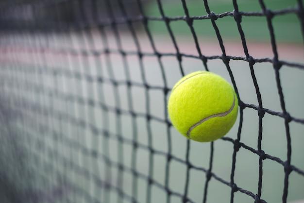 Bouchent la balle de tennis frapper au filet sur fond flou