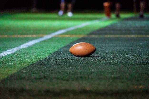 Bouchent le ballon de rugby sur l'herbe verte
