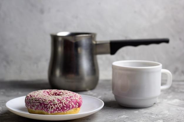 Bouchent beignet sur une plaque floue fond de tasses de café