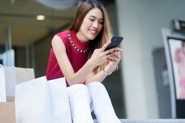 Bouchent belle femme asiatique, jouer au smartphone après avoir magasiné pour se reposer