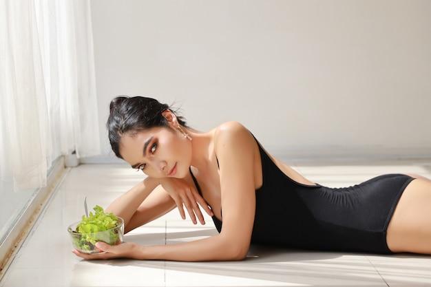 Bouchent belle jeune femme asiatique saine et sportive tenant le bol de salade et manger après la formation