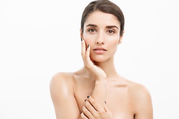 Bouchent belle jeune femme touchant sa peau sur fond blanc.