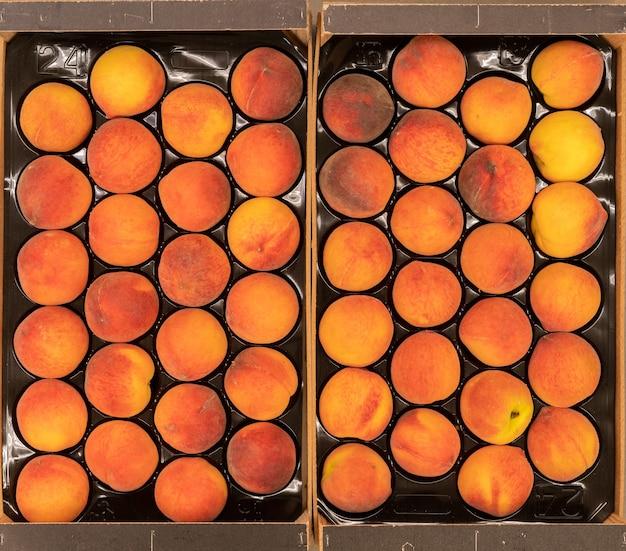 Bouchent de belles pêches crues fraîches dans une caisse en bois