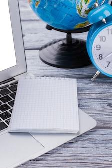 Bouchent le bloc-notes vierge sur un ordinateur portable. concept de temps et de mondialisation. globe terrestre et réveil sur table en bois blanc.