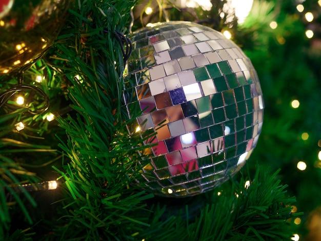 Bouchent la boule brillante argentée sur l'arbre de noël et les guirlandes lumineuses