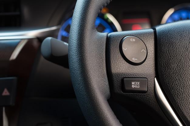 Bouchent le bouton de commande audio sur le volant de la voiture