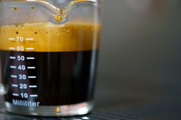 Bouchent café expresso dans un verre avec mesures