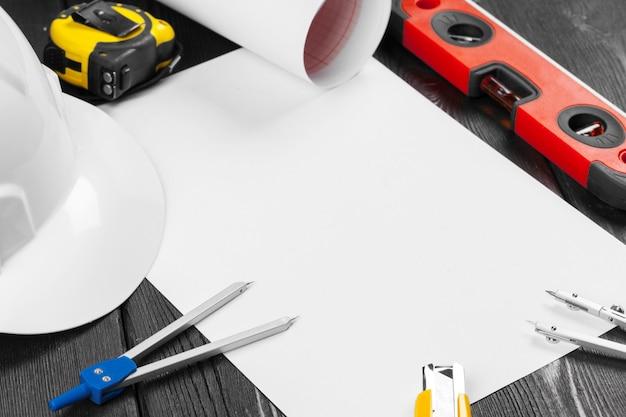 Bouchent casque blanc et variété d'outils de réparation avec fond au milieu sur bois