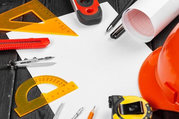 Bouchent le casque orange et une variété d'outils de réparation avec fond au milieu sur bois