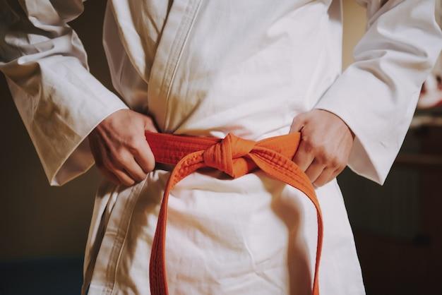 Bouchent la ceinture rouge sur le blanc du combattant d'arts martiaux