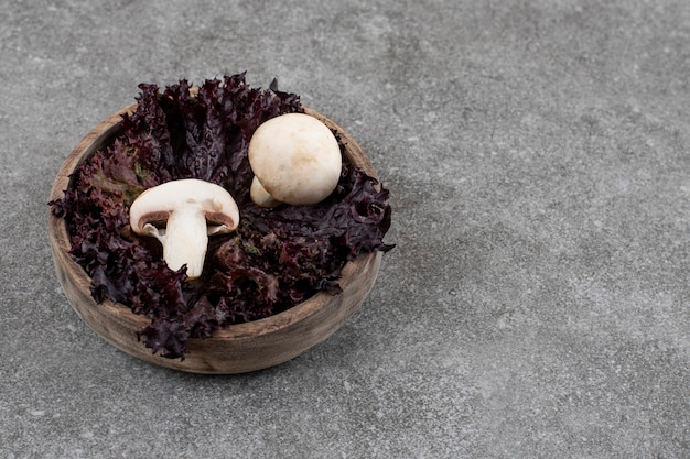 Bouchent les champignons frais avec du vert dans un bol en bois