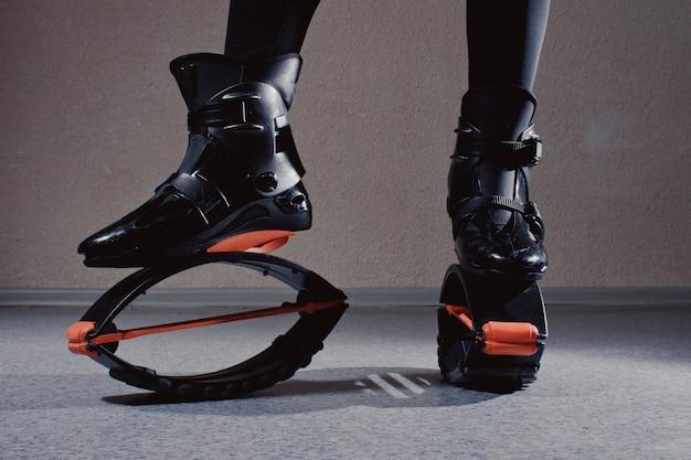 Bouchent les chaussures kangoo. fille belle et sportive dans la formation de gym. saut de kangoo. belles filles en formation kangoo jumping dans la salle de gym