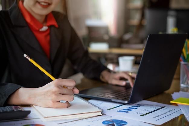 Bouchent crayon de tenue de femme d'affaires écrire quelque chose sur le cahier.