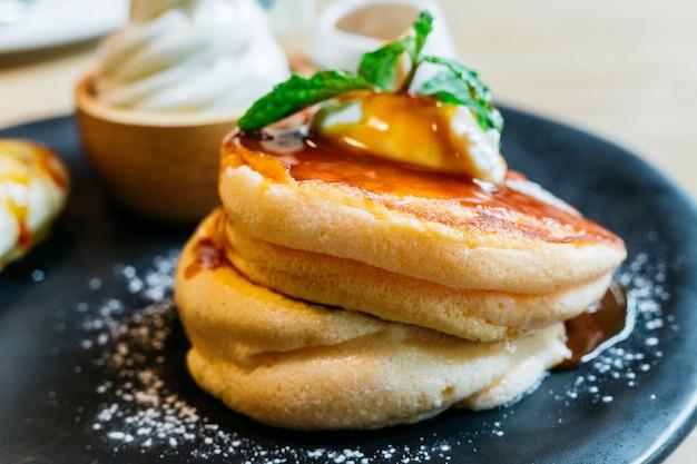 Bouchent les crêpes moelleuses servies avec banane au caramel, crème glacée et sirop.