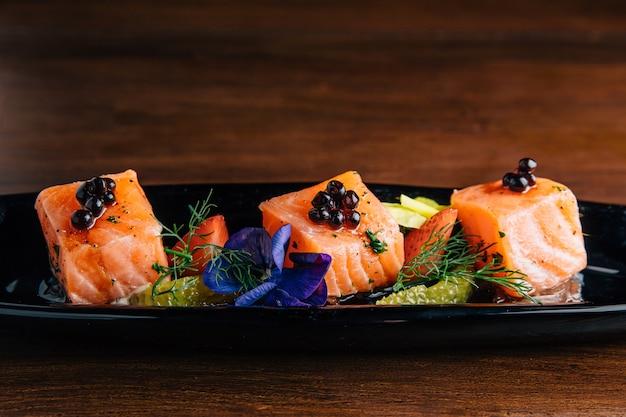 Bouchent le cube de saumon rare et moyen grillé garni de caviar.