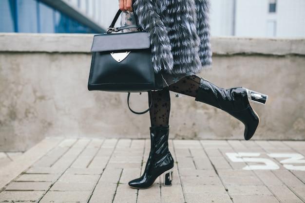 Bouchent les détails des accessoires de femme élégante marchant dans la ville en manteau de fourrure chaud, saison d'hiver, temps froid, tenant un sac à main en cuir, jambes en bottes, tendance de la mode de la rue des chaussures