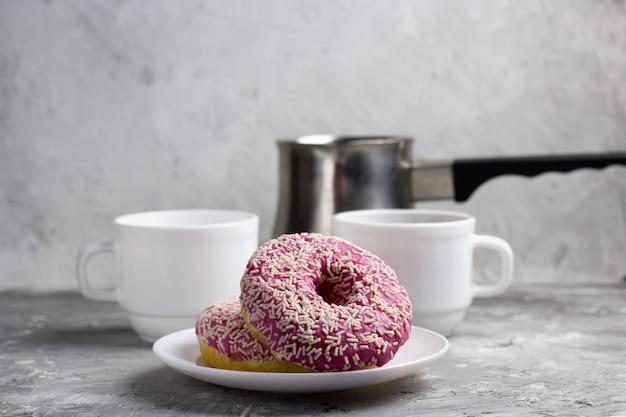 Bouchent deux beignets sur une plaque floue fond de tasses à café