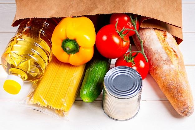 Bouchent divers aliments sains, tomates, pain, pâtes dans un sac en papier sur fond blanc. concept de livraison de nourriture.