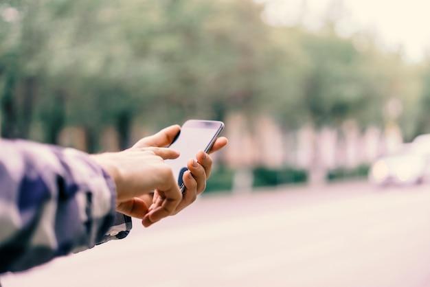 Bouchent les doigts de la main touchant le smartphone dans la ville