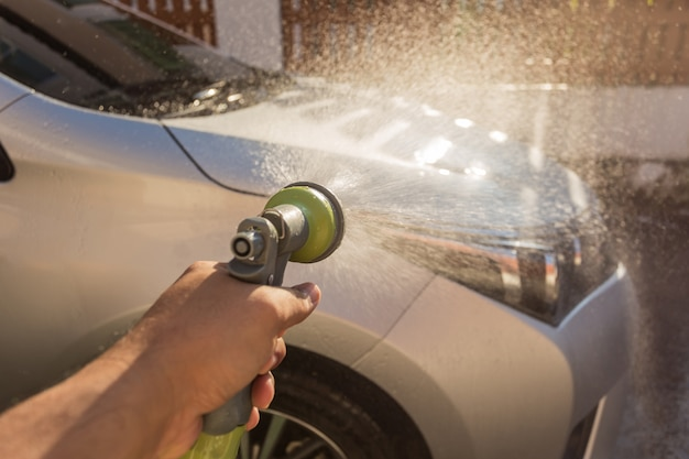 Bouchent l'eau de pulvérisation à la main pour le lavage de voiture. lavage de voiture privé. focus sur le pistolet de pulvérisation