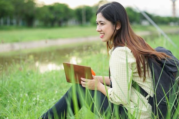 Bouchent femme étudiante asiatique lire livre seul au parc en plein air avec concentré