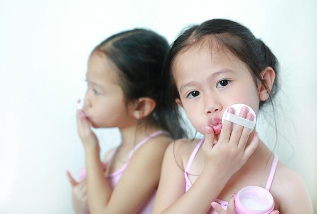Bouchent fille enfant asiatique en appliquant le maquillage sur le visage avec une éponge puff puff.