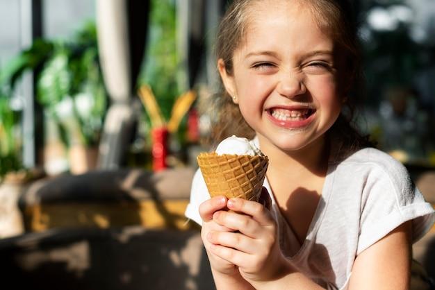 Bouchent fille heureuse avec de la crème glacée