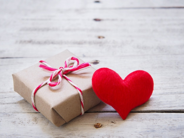 Bouchent la forme de coeur de coussin rouge et boîte-cadeau sur le vieux bois blanc et copie espace pour la saint-valentin.