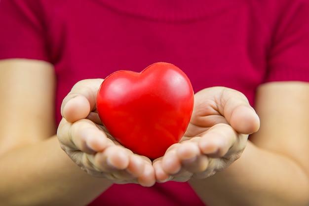 Bouchent une forme de coeur rouge dans une main de femmes.