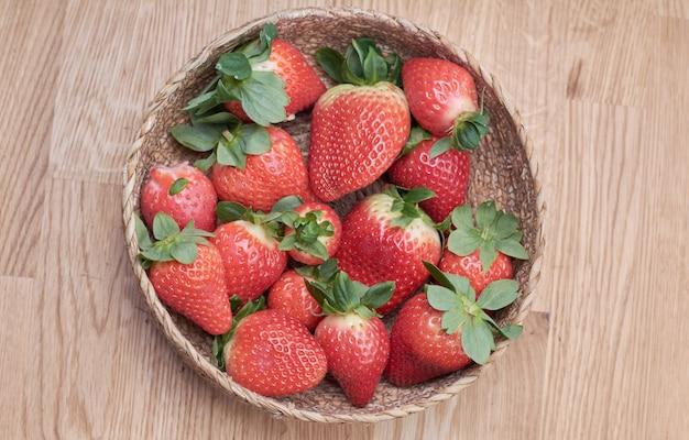 Bouchent les fraises fraîches avec fond de bois naturel dans un panier