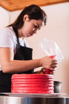 Bouchent le gâteau de décoration de main de femme dans la cuisine.