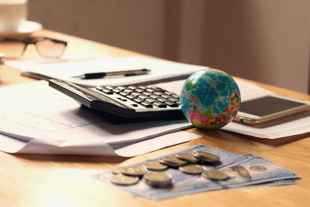 Bouchent globe jouet avec la calculatrice et de l'argent sur le bureau de bureau, concept de comptabilité de la finance