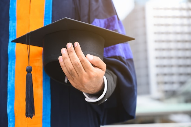 Bouchent la graduation tenant le concept d'éducation cap de l'obtention du diplôme.