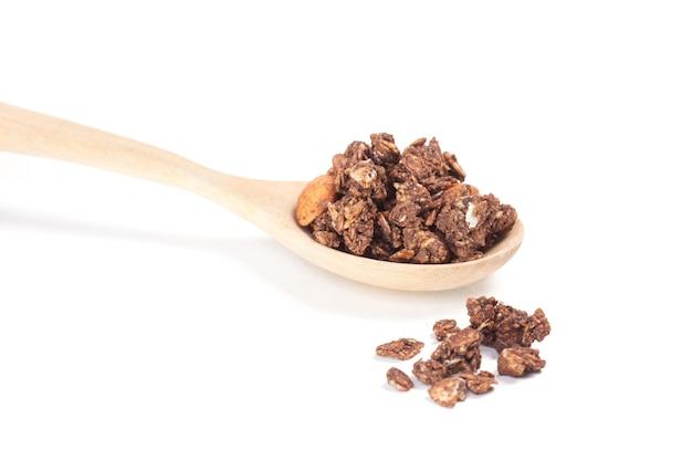 Bouchent granola sur la cuillère de bois isolée sur fond blanc.