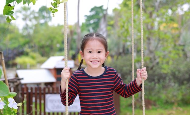 Bouchent heureuse petite fille asiatique enfant jouer et assis sur la balançoire dans le parc naturel.