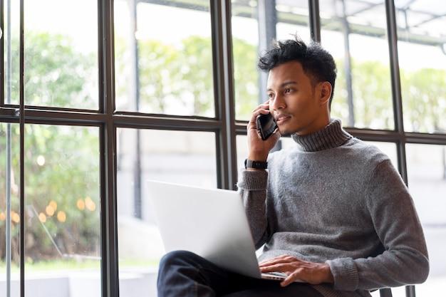 Bouchent homme d'affaires asiatique parler smartphone pour travailler au bureau