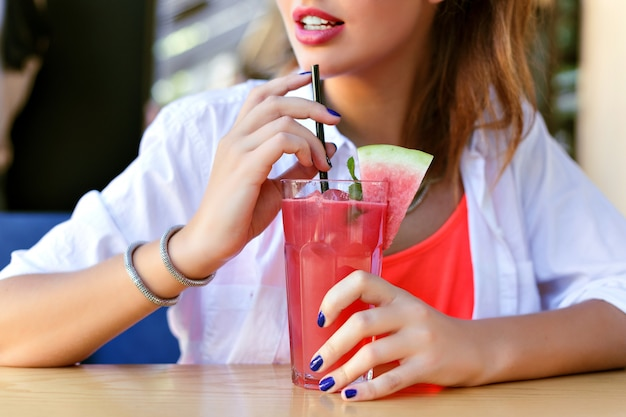 Bouchent l'image lumineuse de femme tenant du jus de fruits frais avec de la pastèque, mode de vie végétalien sain.