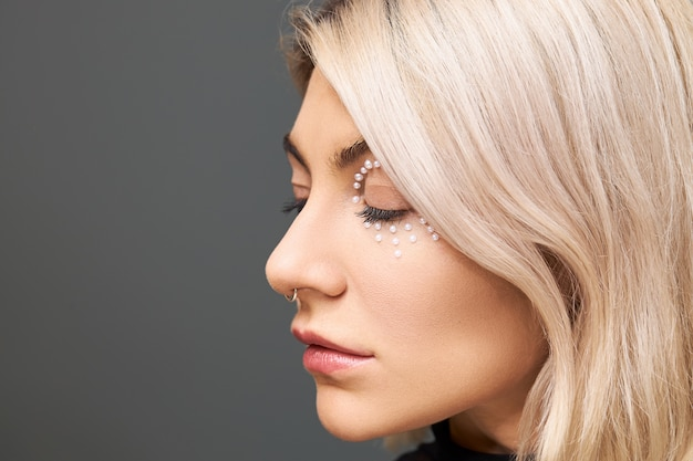 Bouchent l'image de profil de la belle jeune femme avec un maquillage parfait, une coiffure bob teinte, un anneau dans le nez et des cristaux blancs autour de ses yeux, posant isolé, gardant les yeux fermés. beauté, soins de la peau et style