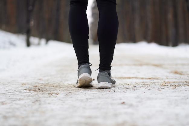 Bouchent les jambes de jogger pendant la course dans la forêt d'hiver