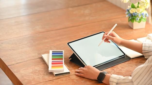 Bouchent jeune femme créative travaillant avec tablette et stylet.