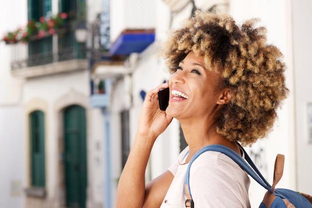 Bouchent joyeuse jeune femme afro-américaine parlant sur téléphone portable