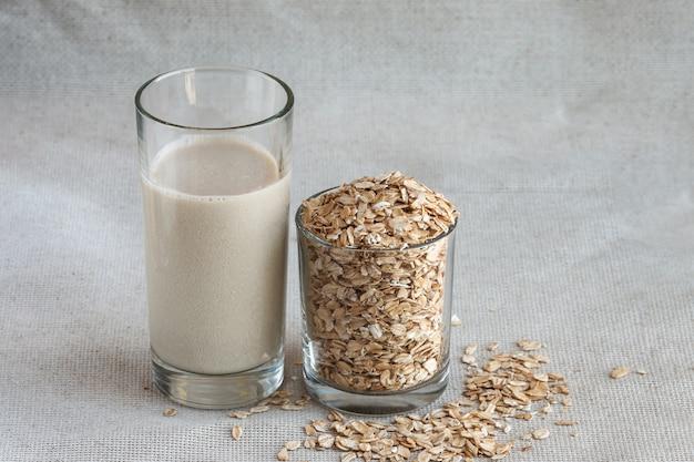 Bouchent le lait d'avoine dans un grand verre à boire avec des graines