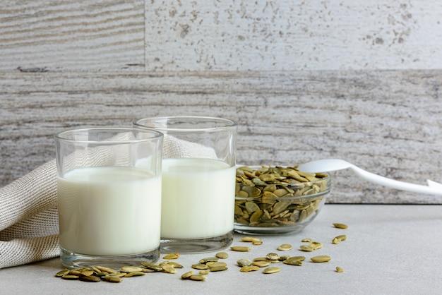 Bouchent le lait de graines de citrouille végétaliennes dans un petit verre à boire avec des ingrédients