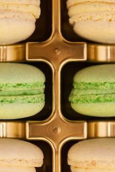 Bouchent les macarons français colorés dans une boîte dorée. dessert sucré