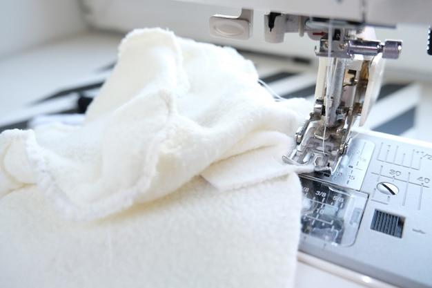 Bouchent la machine à coudre avec du textile blanc au lieu de travail.