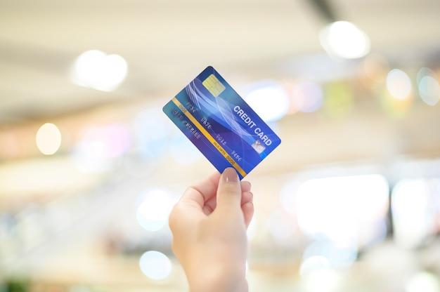 Bouchent la main à l'aide d'une carte de crédit au centre commercial