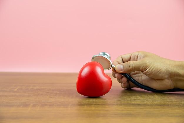 Bouchent la main à l'aide d'un stéthoscope vérifiant un cœur.